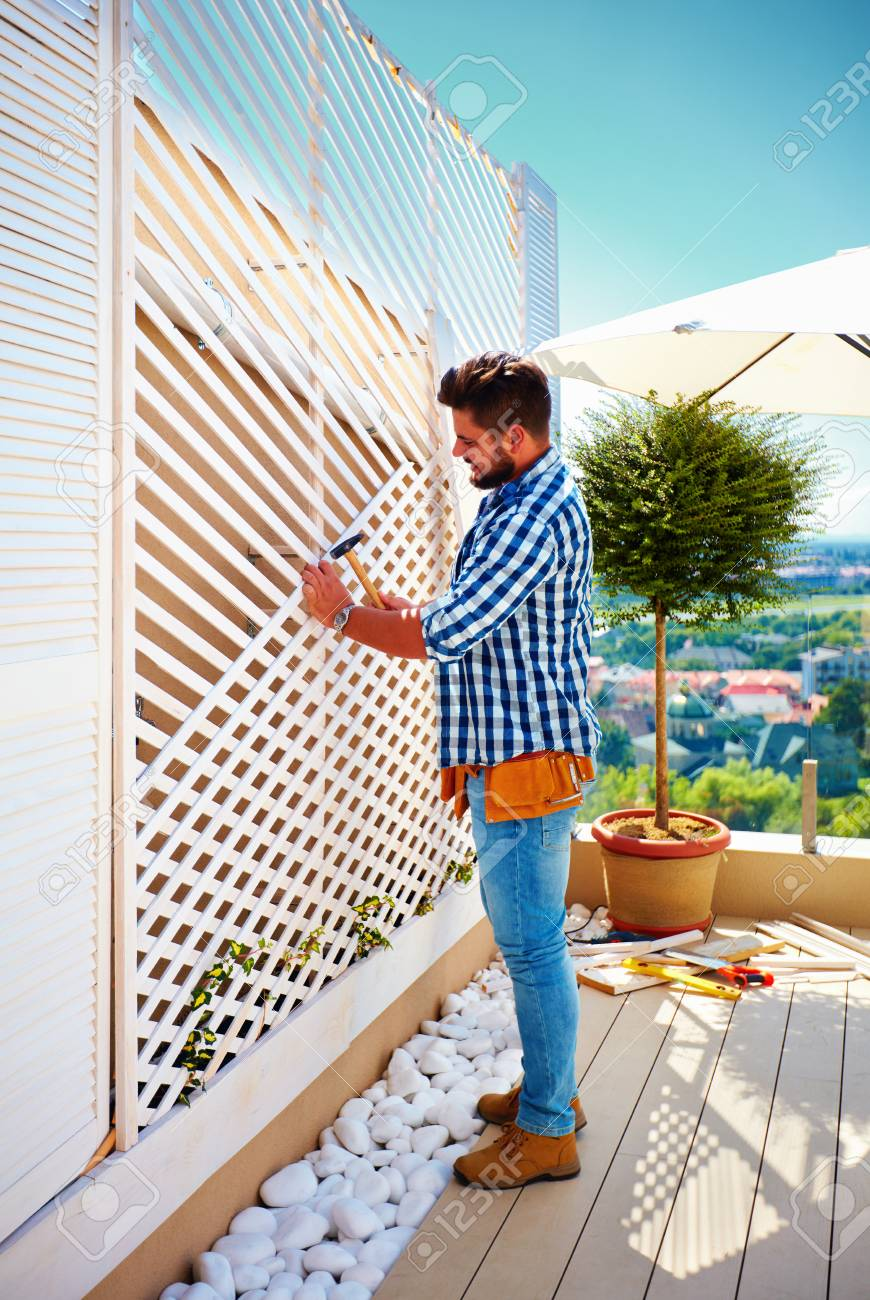 young adult man building wooden pergola wall on rooftop patio