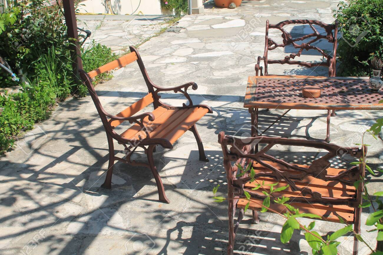 vintage wooden and metal patio furniture set on stone garden