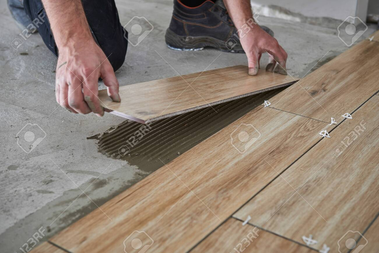 hands of the tiler are laying the ceramic wood effect tiles on stock photo picture and royalty free image image 120552118