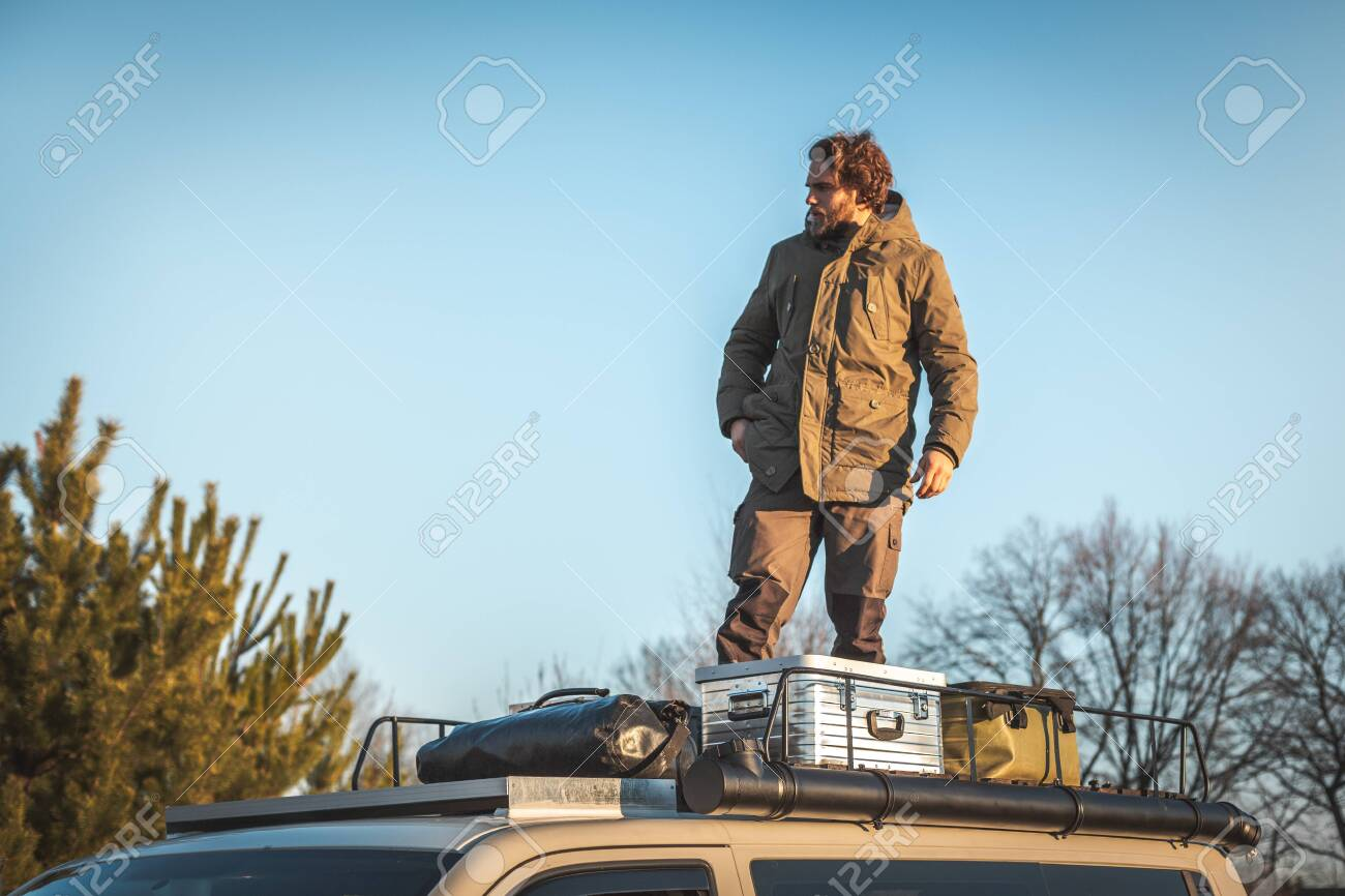 https www 123rf com photo 119692242 young man standing on the roof rack of a van next to boxes and gear html