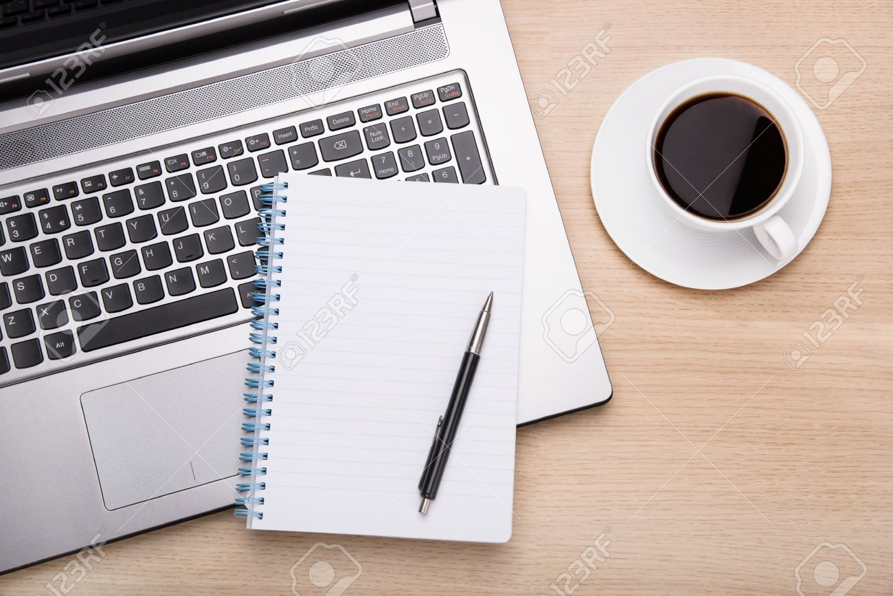 coffee laptop and paperwork on office desk