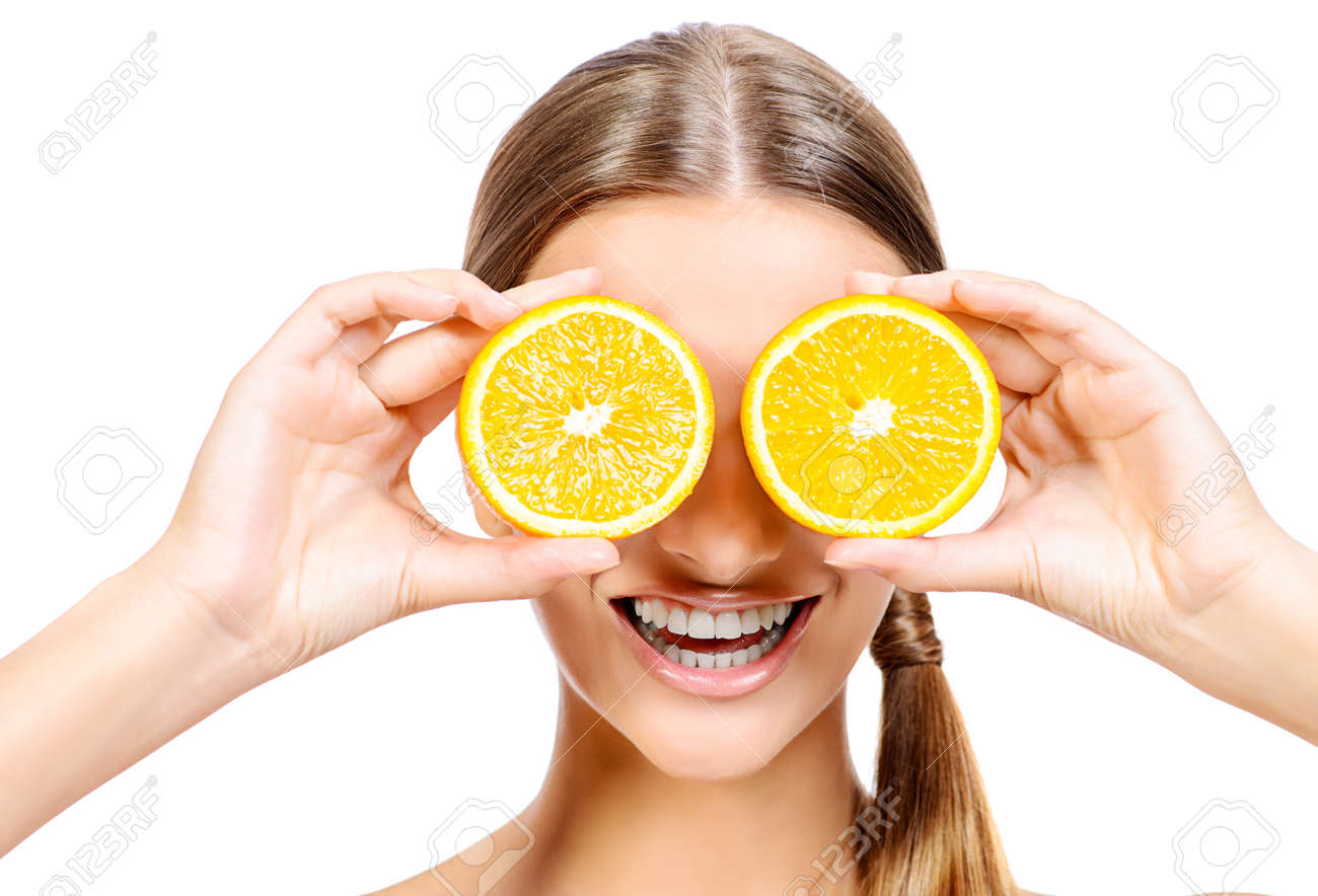 Joyful Young Woman Holding Juicy Oranges Before Her Eyes  Healthy     Joyful young woman holding juicy oranges before her eyes  Healthy eating  concept  Diet