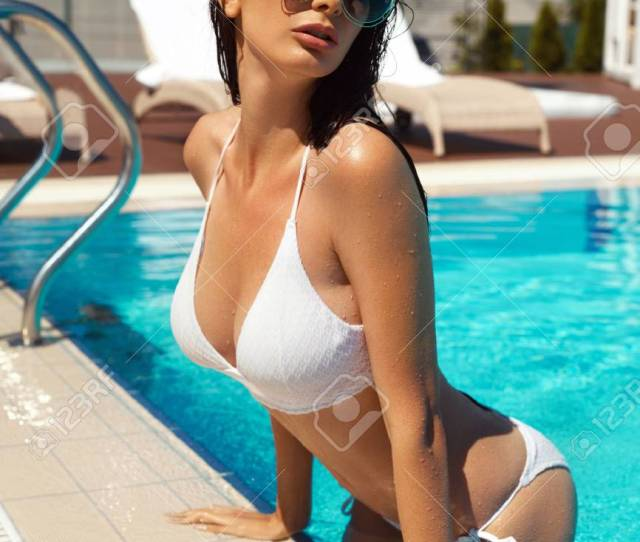 Beautiful Sexy Girl With Hot Fit Body Healthy Skin Tan In Fashionable Elegant White Bikini Sunglasses Relaxing In Water At Swimming Pool Edge At Luxury