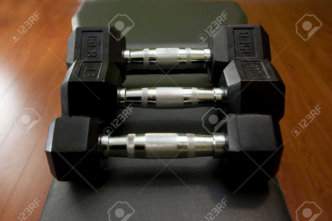 three small weight dumbells on a weight bench with a dumbell