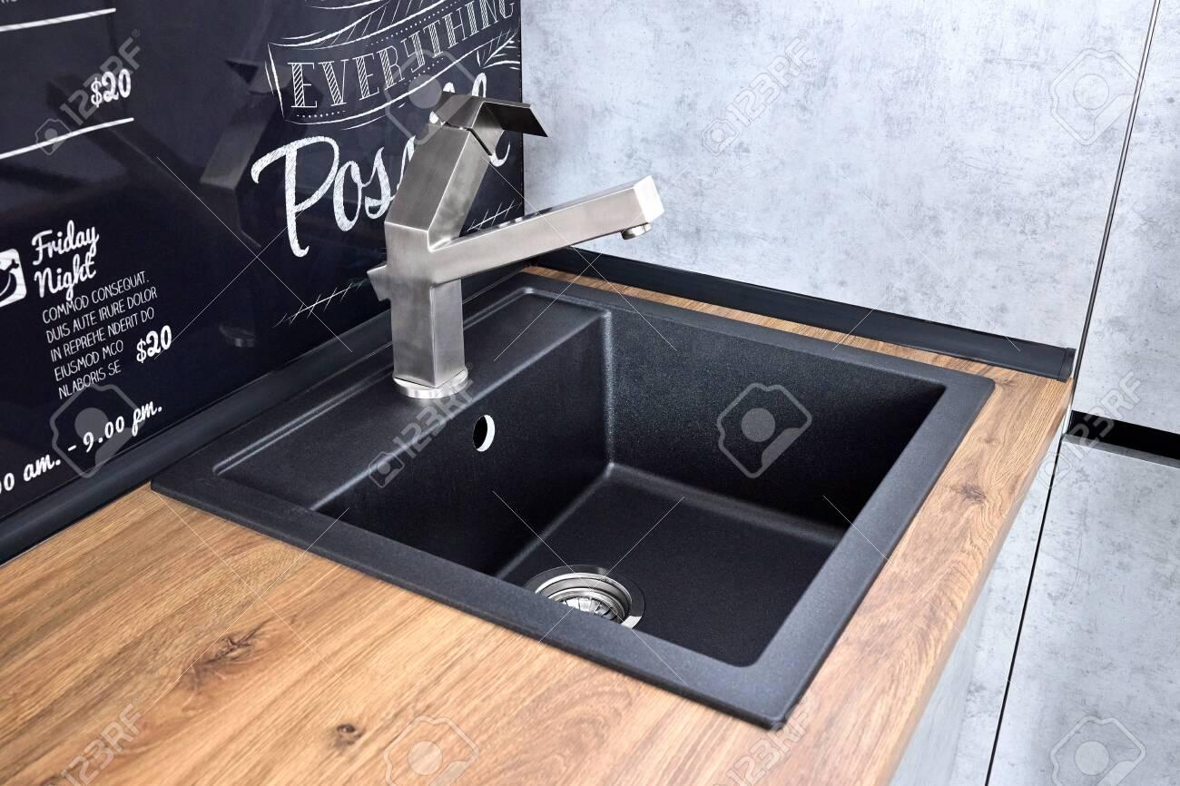 modern design chrome water tap over black stone kitchen sink