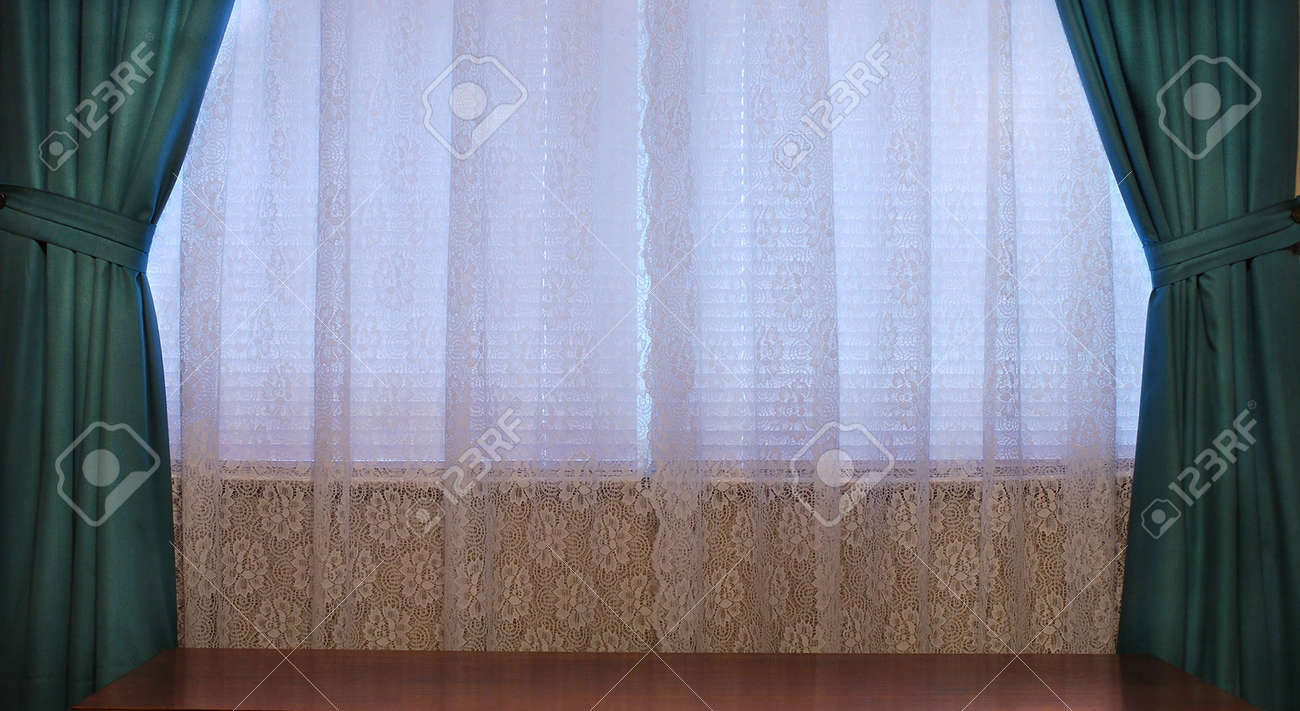house interior window with lace curtains and heavy green drapes