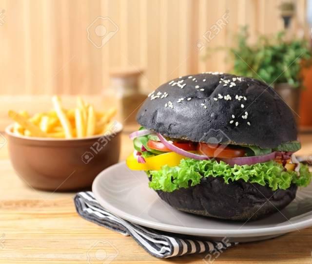 Plate With Tasty Black Burger On Table Standard Bild 112837510