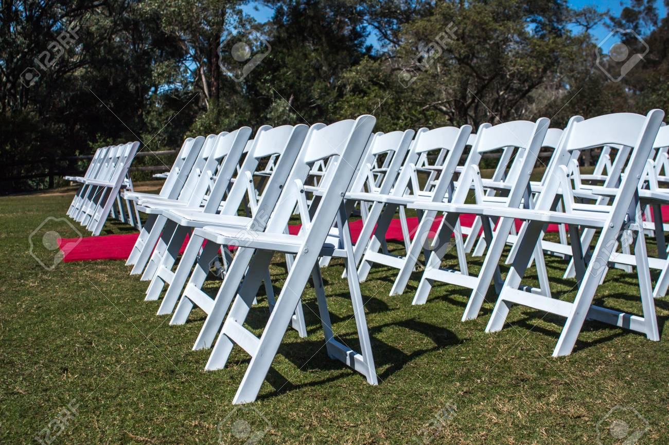 chaises de ceremonie blanches mis en place a l exterieur avec allee de tapis rouge sur l herbe verte avec des arbres en arriere plan banque d images et photos libres de droits image 86494683