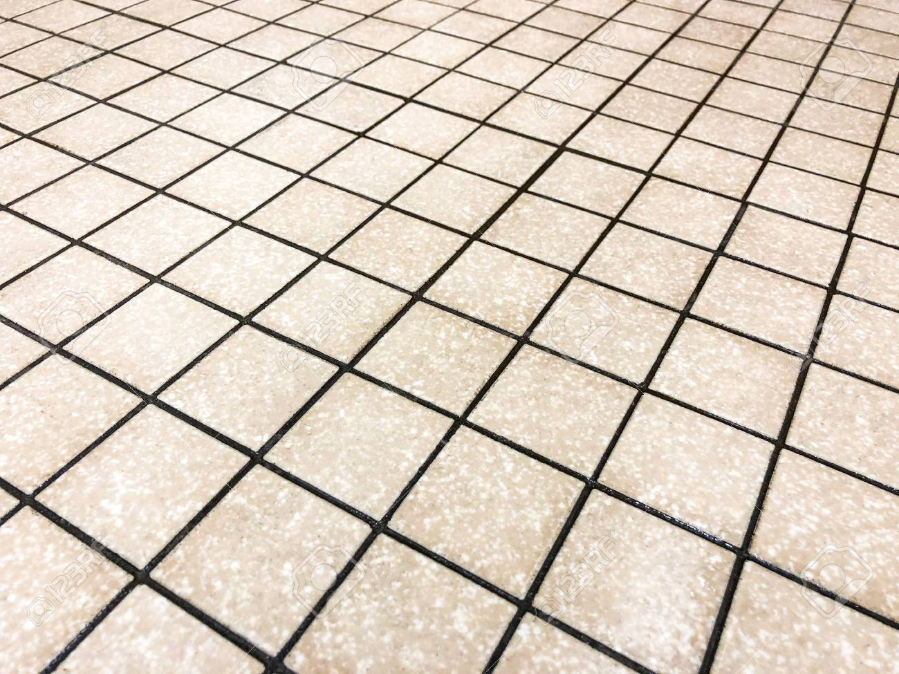 beige square tiles plased straight with black grid like grout
