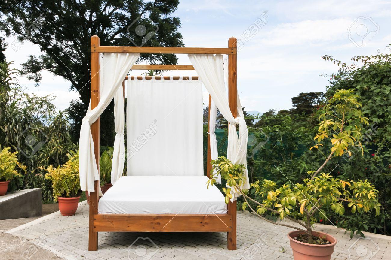 un lit d exterieur en bois avec des draps blancs et les rideaux de la vie privee sur un patio de briques dans une station tropicale