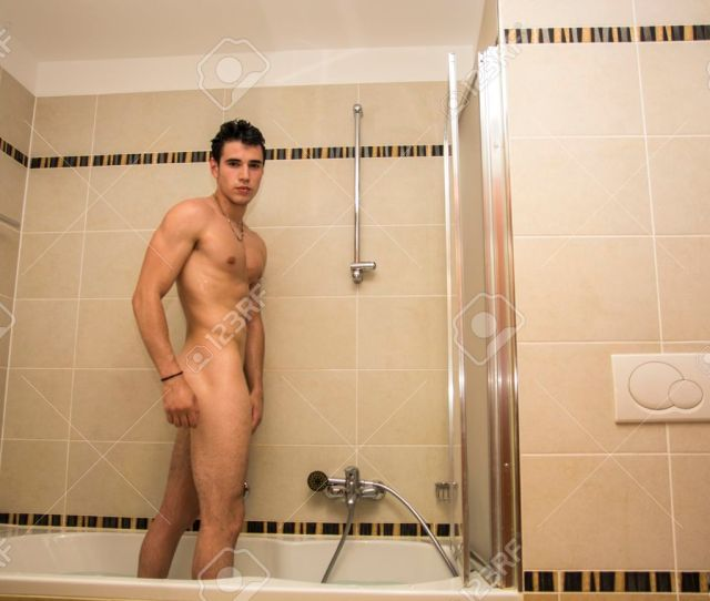 Naked Athletic Young Man Taking Shower At The Bathroom To Refresh Turning Towards Camera Stock