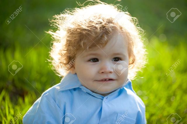 portrait of smiling baby boy with blond curly hair on fresh green..