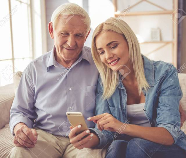 Handsome Old Man And Beautiful Young Girl Are Using A Smartphone Talking And Smiling While