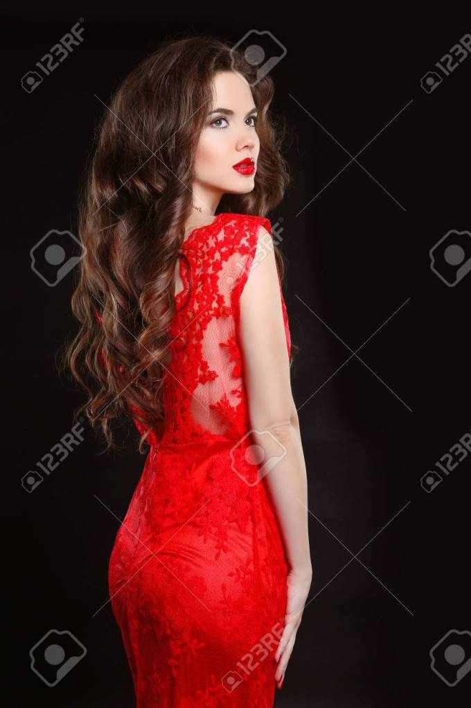 beautiful fashion elegant woman in red dress isolated on black..