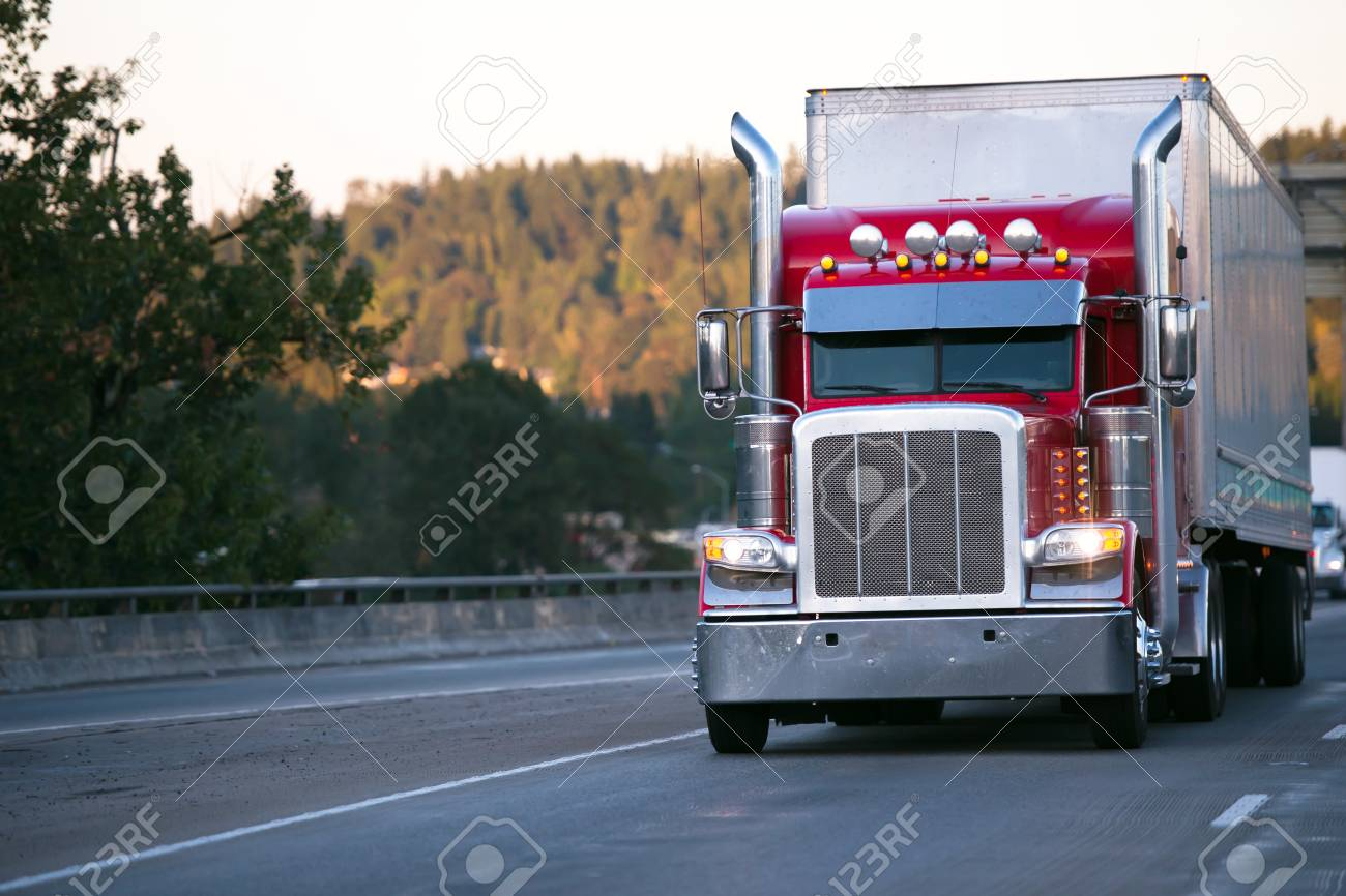 bright red classic big rig semi truck with high exhaust pipes