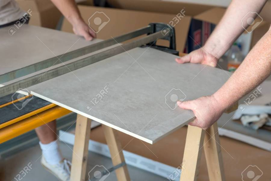 Workers Cutting Ceramic Floor Tiles Tile With Tile cutter  Stock     Stock Photo   Workers cutting ceramic floor tiles tile with tile cutter
