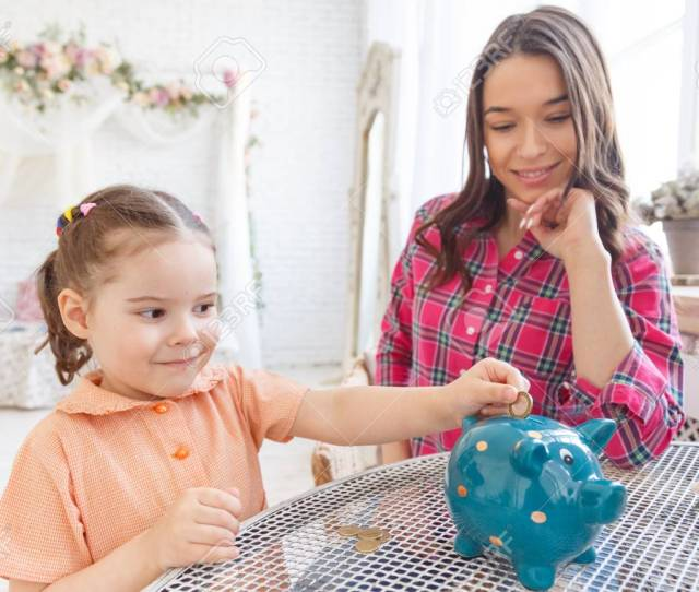 Mom Teaches A Little Daughter To Collect Money In A Piggy Bank Stock Photo 99935106