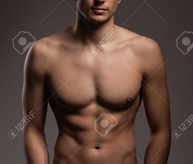 Handsome Young Man With Naked Torso On A Grey Background Stock Photo