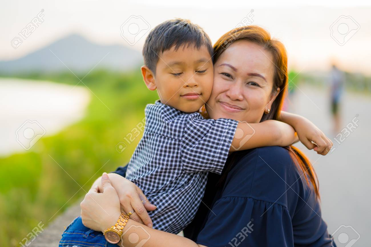Asian Mom Hug Her Young Son Lovingly At Sunset With Nature Background Stock Photo 95810858