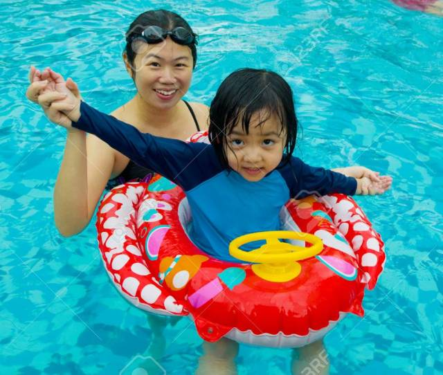 Asian Family In Swim Tube Playing On Swimming Pool Stock Photo 47174556