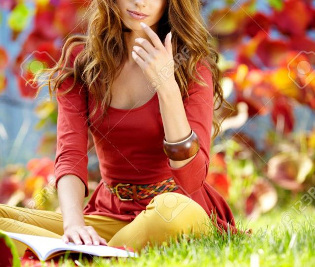 Portrait Of A Gorgeous Brunette Woman Reading A Book In The Autumn Park Stock Photo