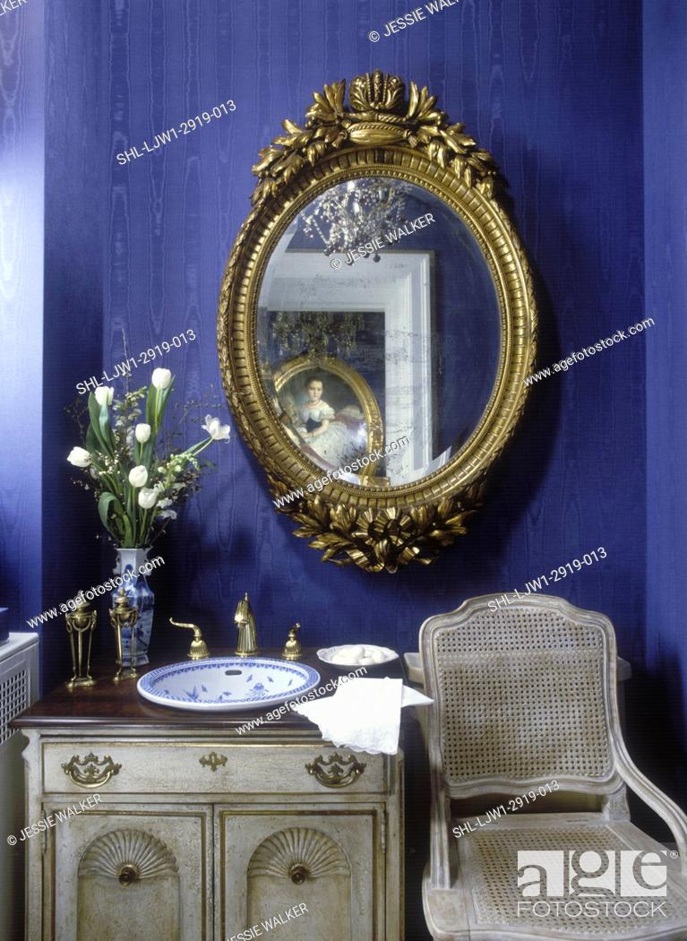 https www agefotostock com age en details photo bathrooms dark navy blue wall paper with moire pattern gold oval mirror sophisticated antiqued french cabinet with basin bowl shl ljw1 2919 013
