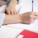 School Girl Hand Writing Math Task To Notepad