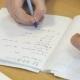 Girl Writes In a School Mathematics Notebook