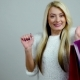 Blonde Model Makes Expressions Of Excitement With Shopping Packages