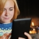 Portrait of a Young Caucasian Woman with the Tablet. Web Surfing on the Background of a Burning