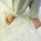 The Baby's Legs Are on a White Carpet at a Slow Pace