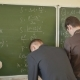 Three Students Write on the Blackboard Mathematical Formulas in the Classroom