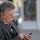 A Smart Old Man Logs on the Web on His Mobile in a City Street in Spring