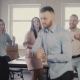 Young European Businessman Dancing Together with Colleagues at Fun Casual Office Party, Celebrating
