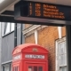 Bus Schedule Display with Red Telephone Booth in London