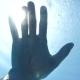 Underwater View of Hand in Sun Rays Shining