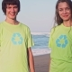 Happy Young Volunteers in Green T-shirts with Image Recycle on an Oceanic Beach Giving High Five