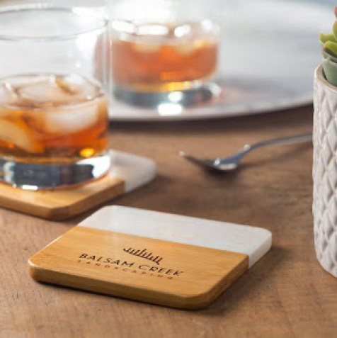 White Marble and Bamboo Coaster Set on a table with a couple glasses of whisky