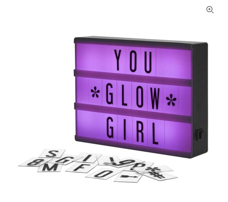 A purple lit cinema box with the word tiles You Glow Girl. Additional letter tiles are scattered in front of the box showing that you can customize it to say anything you want.