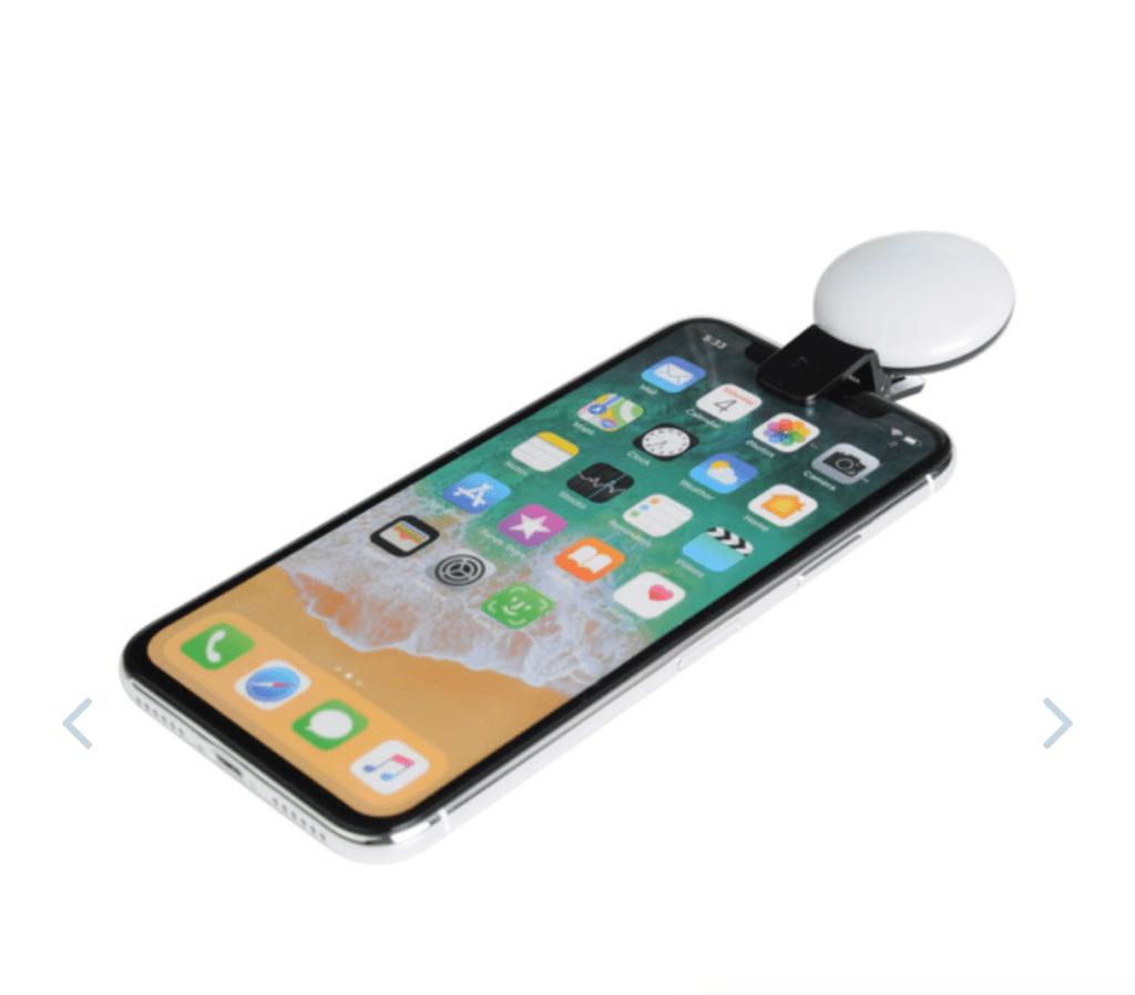 A smart phone with a white circular light attached to the top to enhance lighting and help people appear professional on Zoom calls.