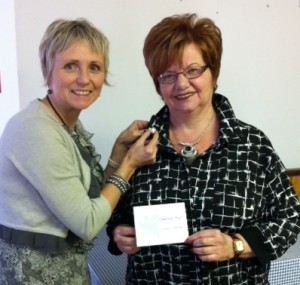 Nancy Warren awarding Barb Schoof a Guardian Angel Pin