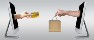 Two hands coming out of laptops, with a credit card and a bag, representing e-commerce.