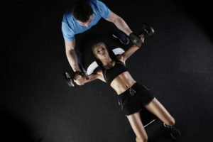A girl working out with a professional trainer in order to later make a home gym on a budget.