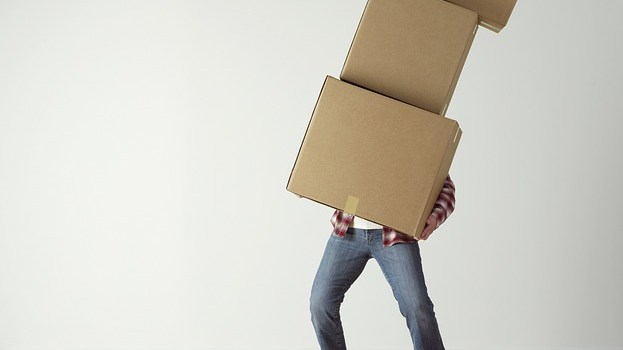 A man carrying some cardboard boxes during his preparations for moving around the corner
