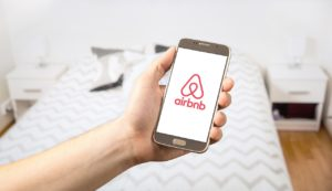 person holding a phone with an airbnb app open