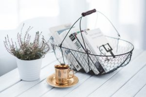A little plant, a book basket and a gold coffee mug sitting on a simple white table.