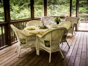 A deck that spreads in and out of the home with pretty white furniture.