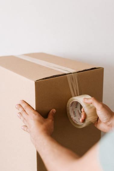 Man taping a box shut.
