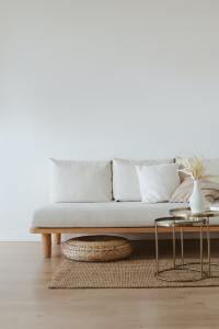 A biege and cream settee with a wicker ottoman and rug and gold side table
