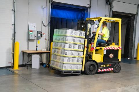 A loaded yellow forklift assisting in shipping pieces of furniture